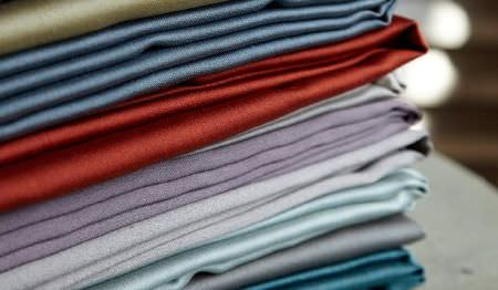 James Hare -  Connaught Silk Fabric Collection - Plain, slightly shiny fabrics in colours such as lilac, brick red, blue, white and grey, folded and stacked in a neat pile
