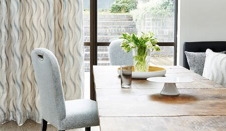 James Hare -  Corolla Fabric Collection - Beige fabric decorated with a modern wavy pattern in grey and a set of grey upholstered dining chairs
