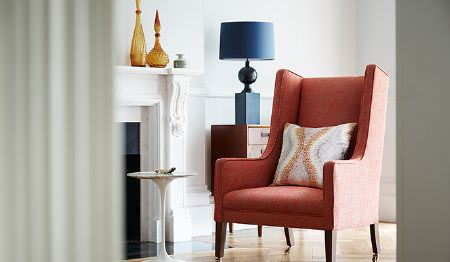 James Hare -  Corolla Fabric Collection - Plain upholstered armchair in modern shade of orange and a beige cushion with abstract orange pattern
