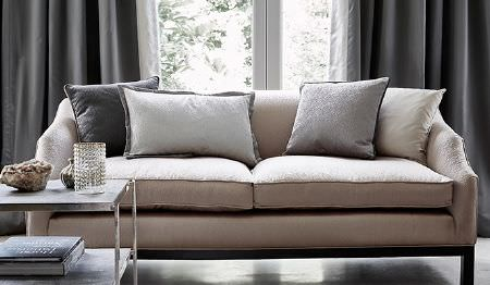 James Hare -  Elements Fabric Collection - A large, plain beige sofa with gunmetal grey coloured curtains, 4 plain cushions in various shades of grey, and a table