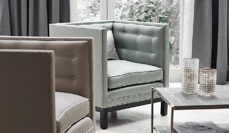 James Hare -  Elements Fabric Collection - Two plain padded cube shaped armchairs in pale shades of blue and beige, with dark grey curtains and a light grey table