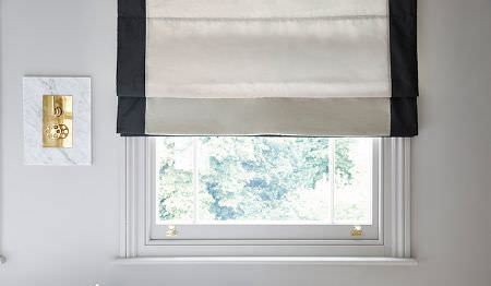 James Hare -  Elements Fabric Collection - A window with an off-white coloured window blind finished with black trim down both sides, beside gold and marble controls
