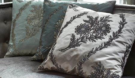 James Hare -  Evolution Fabric Collection - A light grey sofa with 3 luxurious, embroidered, floral patterned cushions in silver, dusky blue, sky blue and dark grey