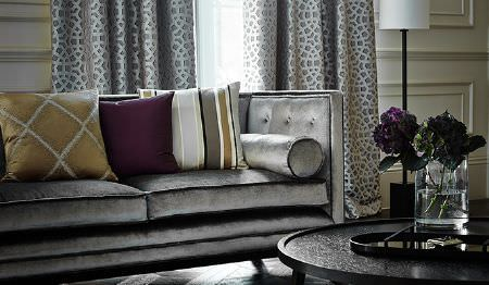 James Hare -  Evolution Fabric Collection - A large silver sofa with grey and white patterned curtains, a round coffee table, and grey, purple and white cushions