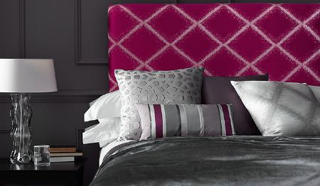 James Hare -  Evolution Fabric Collection - A headboard in two shades of pink, with a bed with dark grey bedding, silver, grey and purple cushions, a table and a lamp