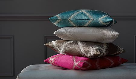 James Hare -  Evolution Fabric Collection - A white padded bench seat stacked with hot pink, dark grey, white and aqua blue cushions, all streaked with white lines