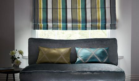 James Hare -  Evolution Fabric Collection - Aqua and olive green patterned cushions, a matching striped window blind, a plain grey sofa, a round table and a vase