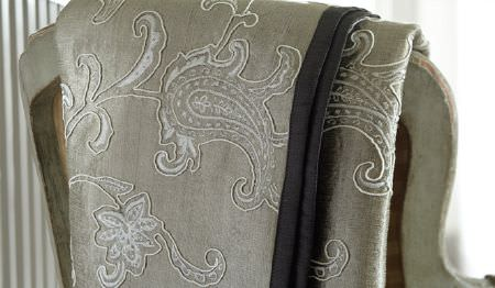 James Hare -  Halkin Silks Fabric Collection - Detailed white patterns embroidered on grey fabric, draped over the back of a distressed light grey wood framed chair