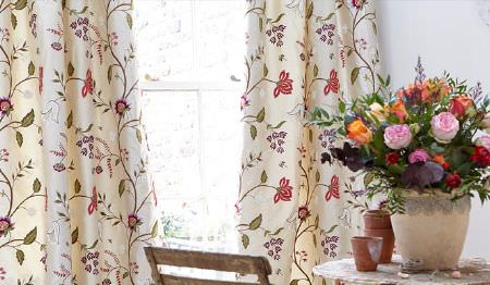 James Hare -  Orchard Silk Fabric Collection - Cream, red, purple and green floral patterned curtains with a wooden chair beside a rustic table with a large flowerpot
