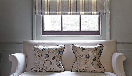 James Hare -  Orchard Silk Fabric Collection - A striped window blind in white and pale blue with a white sofa and two white, blue and grey floral patterned cushions