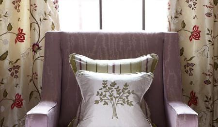 James Hare -  Orchard Silk Fabric Collection - A boxy mauve armchair with two green and white striped and tree patterned cushions and cream floral patterned curtains