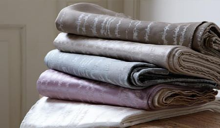 James Hare -  Orchard Silk Fabric Collection - White, lilac, powder blue, silver and dark grey fabrics folded up and stacked on each other in a neat pile