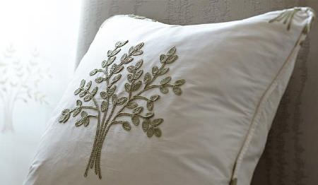 James Hare -  Orchard Silk Fabric Collection - A single white square scatter cushion featuring a simple pattern of an individual tree design embroidered in khaki-grey