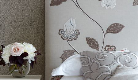 James Hare -  Oriel Silks Fabric Collection - A glass bowl vase beside a bed with white bedding, a floral headboard and a patterned cushion, both in light grey shades