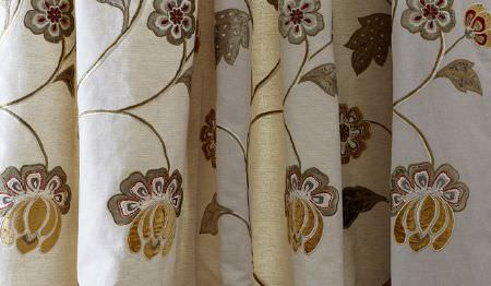 James Hare -  Oriel Silks Fabric Collection - Swathes of chalk white fabric featuring astylised floral pattern ingold and grey with a few subtle dark red highlights