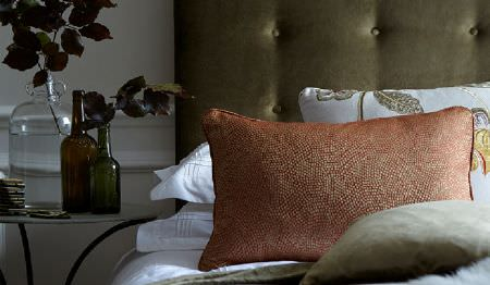 James Hare -  Oriel Silks Fabric Collection - A dark green-grey headboard and cushion,a speckled red-gold cushion, white bedding, a round table and glass vases