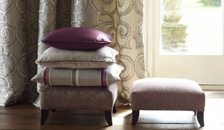 James Hare -  Oriel Silks Fabric Collection - Two low footstools with grey and cream patterned curtains and threeplain and striped grey and purple cushions