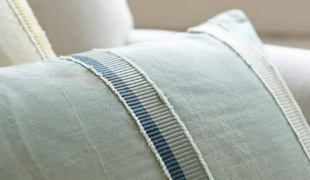 James Hare -  Oriel Silks Fabric Collection - A plain white armchair with awhite and pale green striped cushion, and acushion striped in white and3 shades of blue