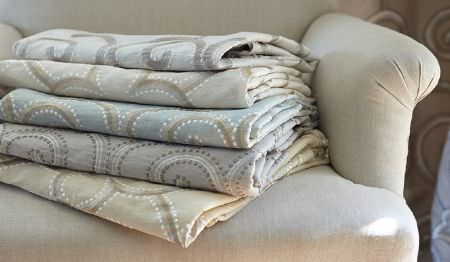 James Hare -  Oriel Silks Fabric Collection - A cream padded armchair with folded fabrics featuring swirling patterns in pale shades of grey, blue, cream and white