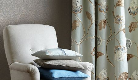 James Hare -  Oriel Silks Fabric Collection - Pale blue and brown floral curtains beside a white padded armchair with plain cobalt blue, baby blue and grey cushions