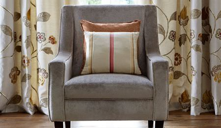 James Hare -  Oriel Silks Fabric Collection - Grey, brown and cream floral curtains behind a plain grey armchair with a copper coloured cushion and a striped cushion
