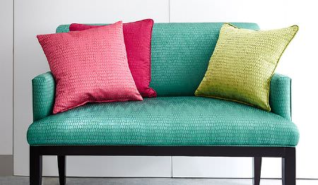 James Hare -  Osprey Fabric Collection - A bright turquoise sofa with black legs and three textured scatter cushions, made in citrus green and two shades of pink