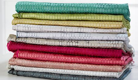 James Hare -  Osprey Fabric Collection - Grey, white, pink, mauve, gold and green shades making up 11 lustrous, subtly patterned fabrics folded and stacked in a pile