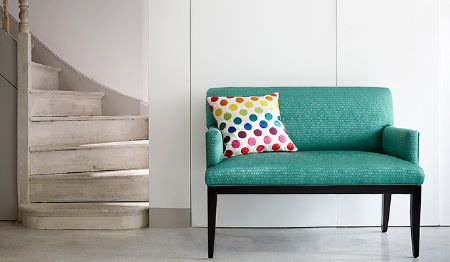 James Hare -  Osprey Fabric Collection - A staircase, a subtly patterned turquoise sofa with black legs, with a fun multicoloured spot print scatter cushion