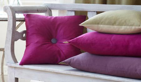 James Hare -  Pelham Silk Fabric Collection - Plain magenta and lavender cushions, with a double-sided light green and yellow cushion, on a white wooden bench