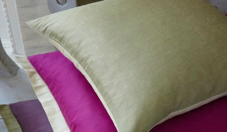 James Hare -  Pelham Silk Fabric Collection - A double-sided green and light yellow cushion with a magenta cushion with yellow trim, and apurple cushion with green trim