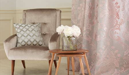 James Hare -  Pimlico Fabric Collection - Luxurious pink and silver patterned curtains with a beige padded armchair, a patterned cushion, and wooden stacking tables