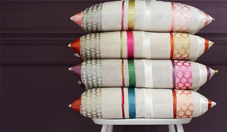 James Hare -  Pimlico Fabric Collection - Patterns and stripes running across four cream cushions in orange, pink, purple, blue, green and white, on a white stool