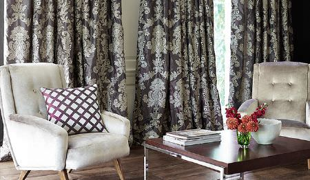 James Hare -  Pimlico Fabric Collection - Charcoal and silver patterned curtains, two grey-white armchairs, a square wood and metal coffee table and a patterned cushion