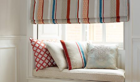 James Hare -  Pimlico Fabric Collection - Grey, orange, red, blue and white striped blinds with matching striped, patterned and plain cushions on a white window seat