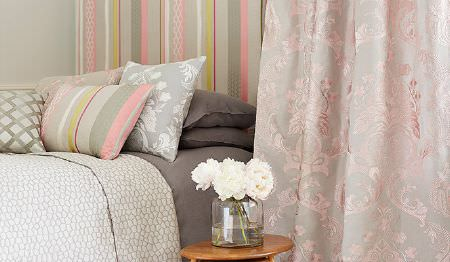 James Hare -  Pimlico Fabric Collection - Grey bedding with pale shades of pink and grey making up a striped cushion and wallpaper and patterned curtains