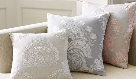 James Hare -  Pimlico Fabric Collection - White and off-white, white and grey, and pink and grey ornately patterned square scatter cushions on a cream sofa