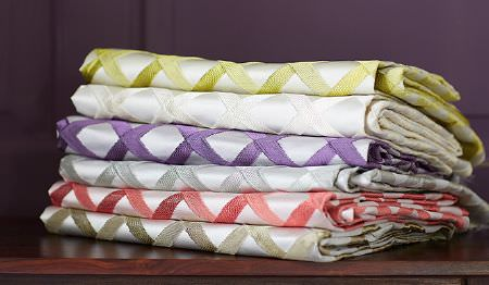 James Hare -  Pimlico Fabric Collection - A wooden shelf with a stack of folded fabrics featuring grid patterns in white, beige, red, silver, purple and lime green