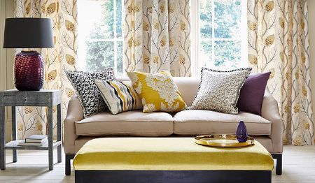 James Hare -  Portobello Fabric Collection - Gold and cream leaf print curtains, a cream sofa, a light gold and black padded bench seat, 5 patterned cushions, and a lamp