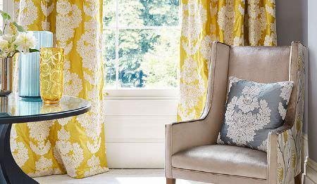James Hare -  Portobello Fabric Collection - Ornately patterned white and lustrous gold curtains, a co-ordinating cushion, a beige and leaf print armchair, and a table