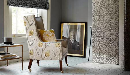 James Hare -  Portobello Fabric Collection - A tall black and white patterned screen, with a pale grey and light gold leaf print armchair, and a gold and white cushion