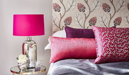 James Hare -  Portobello Fabric Collection - Silver table lamp with a hot pink shade, by a bed with a leaf print headboard and lustrous pink, purple and mauve bedding