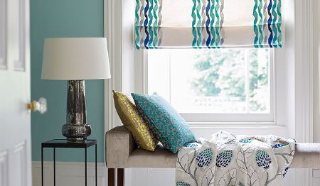James Hare -  Portobello Fabric Collection - White, grey, aqua and blue on blinds with twisted stripes, a leaf print throw, next to a bench seat, 2 cushions and a lamp
