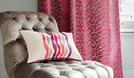 James Hare -  Portobello Fabric Collection - A padded light grey chair with a white cushion printed with pink and purple twisted stripes, and pink and grey curtains