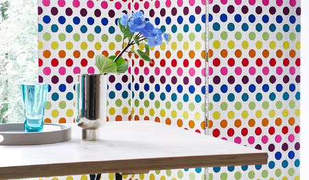 James Hare -  Portobello Fabric Collection - A bright, multicoloured, spot patterned screen beside a simple white table, a silver vase, a round tray and a blue glass