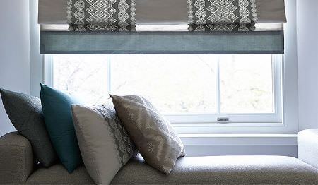 James Hare -  Prism Silks Fabric Collection - A light grey bench style padded seat with blue and light grey patterned cushions and a grey patterned stripe window blind