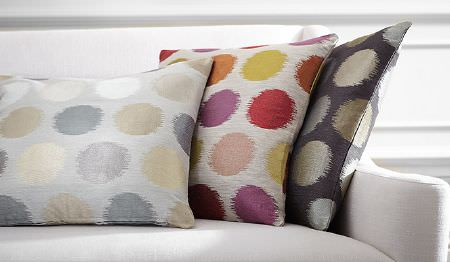 James Hare -  Prism Silks Fabric Collection - A plain white sofa with three circle print cushions in light shades of cream and beige, bright colours, and black and cream