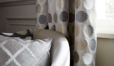 James Hare -  Prism Silks Fabric Collection - A white tub chair with circle print curtains in light shades of grey and cream, with a darker cushion and a silver cushion