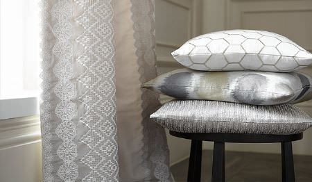 James Hare -  Prism Silks Fabric Collection - Curtains patterned in white and very pale grey, with a black stool, with three different grey and white patterned cushions