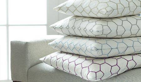 James Hare -  Prism Silks Fabric Collection - Four white cushions with purple, blue, grey and green hexagonal prints, stacked on a plain pale grey-white sofa