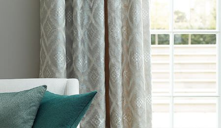 James Hare -  Prism Silks Fabric Collection - Teal and blue-grey cushions on a bright white sofa in front of silver and white diamond print patterned curtains